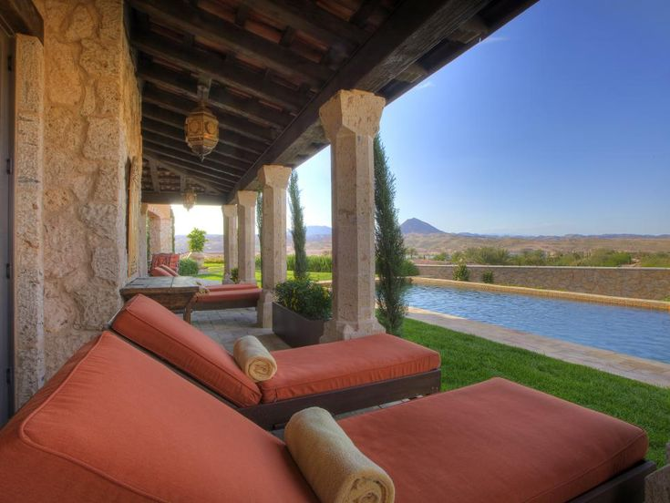 Four lounge chairs covered with rust-orange cushions face a rectangular swimming pool in this Tuscan style patio. Rolled up blanket that sit on the chairs double as pillows.