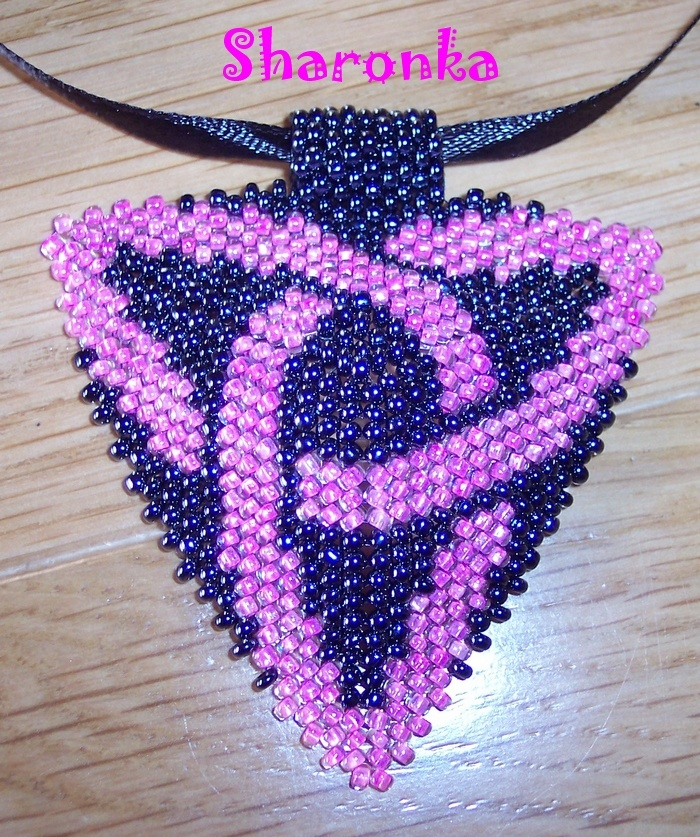 Trojúhelník III. Trojúhelník šitý zčeského růžového a hematitového rokajlu (strana má 6 cm) zavěšený na saténové stužce. Délka náhrdelníku 48 cm.