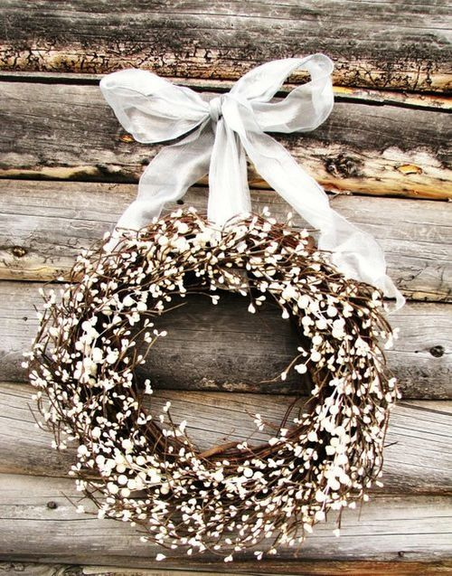 Year-round outdoor wreath design: single color flower or greenery tied onto twigs and hung with a wire hidden in a water-resistant ribbon