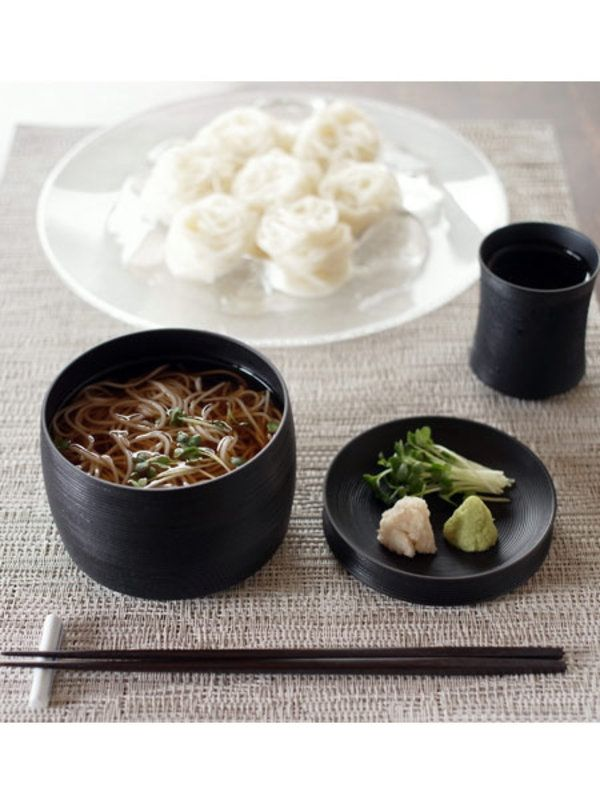 """Q. 和食器の魅力ってどんなところ? 和食器のよさは、器を通して和のライフスタイルをイメージできるところだと思っています。箸置きをどうするか、どう料理を盛り付けようかといったように、作法も含めて「美しい」と思う心、まさに日本人の原風景ですよね。器はそのイメージの一部として、身近にいてくれるものなんじゃないかなって思います。 ちなみに写真は""""つらり""""の使用例で、日本の夏の風物詩である素麺をいただくシーンを表しました。右の薬味皿は、まずは素麺の入った器のフタとしての機能をもち、後からお皿としての役目を果たしています。こんなふうに、皆さんにも自由に使っていただきたいですね。 Q. 今後目指すところは? 今回のコラボだけで終わらずに、今後は「我戸幹男商店」のブランディングにも関わっていきます。「我戸幹男商店」は山中漆器の産業を背負う存在だと思うので、20年先や海外展開までを視野に入れた彼らのものづくりを、多角的な形でサポートするつもりです。和モダンはいつだって廃れない、その強い魅力を武器に、これからも和食器と向き合っていきます。 >>記事を最初から読む"""