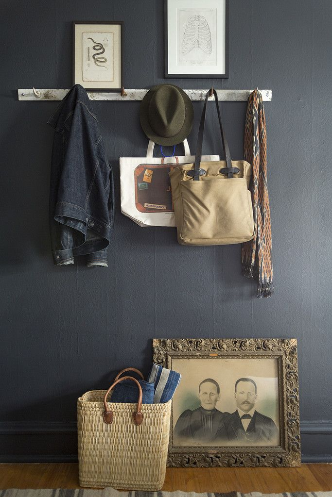 Personal accessories hang from antique butcher's hooks in Carollo's bedroom. | Lonny