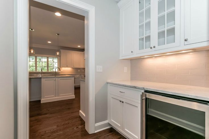Traditional Kitchen with High ceiling, flush light, Simple marble counters, Craftsman Panel Cabinet Door, Wine refrigerator
