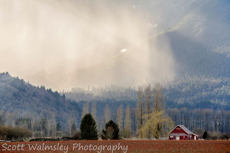 Rain falling in the mountains behind farmland, Fraser Valley, British Columbia
