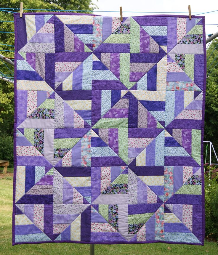 "My take on a scrap strip quilt which is also on this page called ""strip twist""! I did this in floral purples and pastels. I like the illusion that its diamonds on point - it isn't. Quick to make."