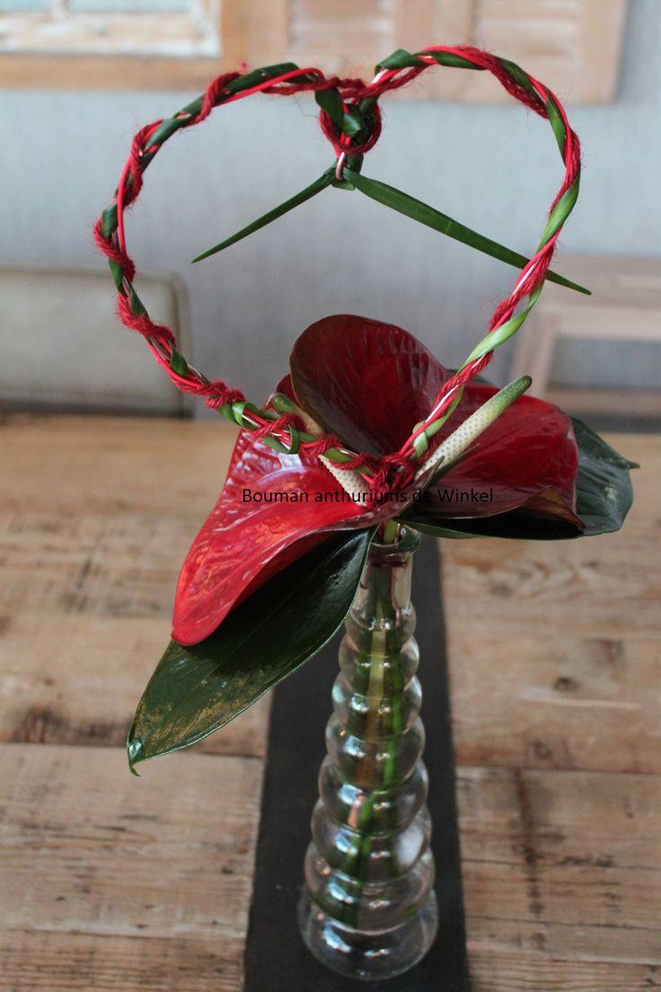 Een glazen fles opgemaakt met anthuriums en een decoratief hart van ijzerdraad, touw en lillygrass.
