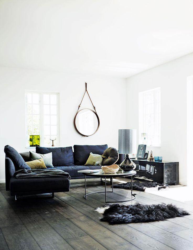pokój dzienny w stylu skandynawskim | białe ściany + ciemna, drewniana podłoga + granatowa minimalistyczna sofa + okrągłe, wiszące lustro