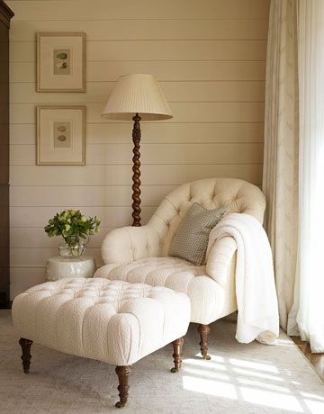 Peaceful reading nook with a tufted chair & ottoman, wood paneled walls, and spiral reading lamp