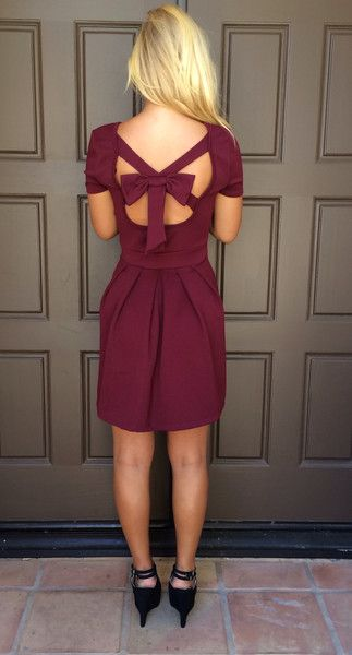 This dress features a scoop back detail with a bow, a cross front, a pleated skirt, an an invisible zipper at the side.