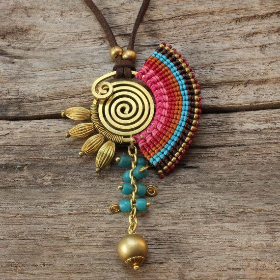 This is a fun necklace that features a series of cotton weaving around a shaped brass spiral. The necklace also features a turquoise drop that has