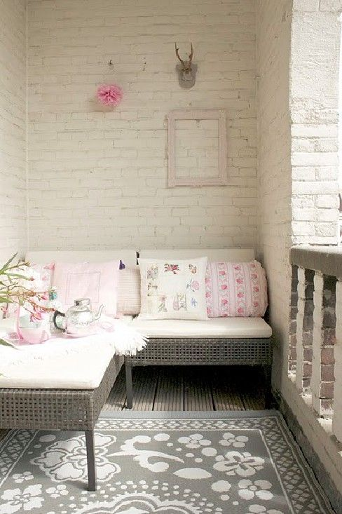 Whitewashing the brick on this cozy white, gray and pink porch makes it seem larger and brighter.
