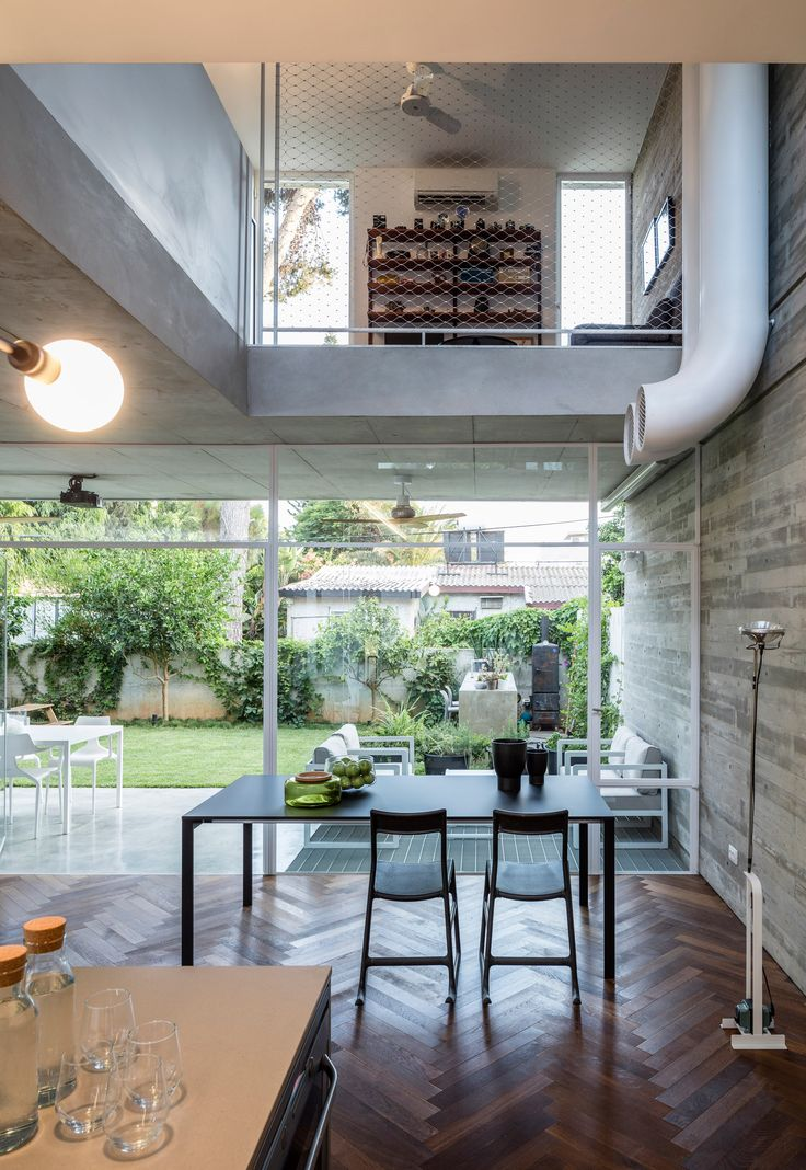 Huge windows and patios in this concrete house in Tel Aviv shed natural light across the interior while also allowing the family full views of the surrounding garden.