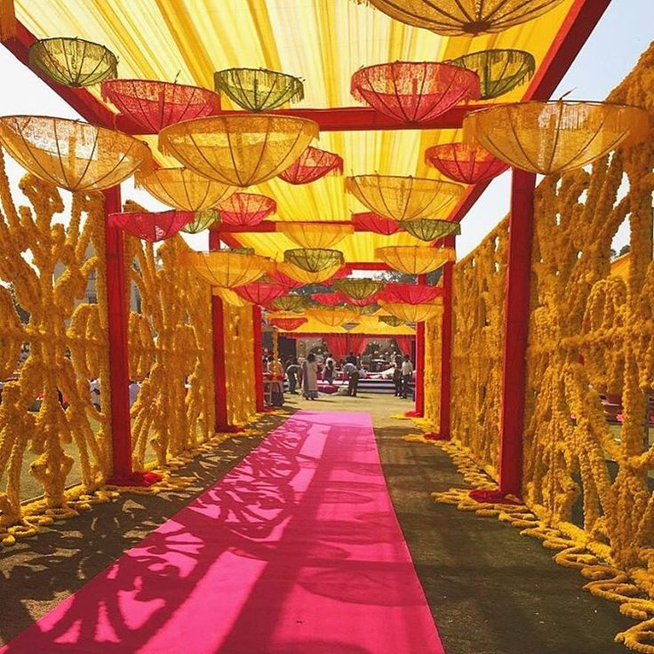 Red carpet replaced with pink and boring props replaced with quirky umbrellas look so much charming | wedding venue entrance decor | look for marriage halls and banquet halls in Mumbai on wedfine.com |
