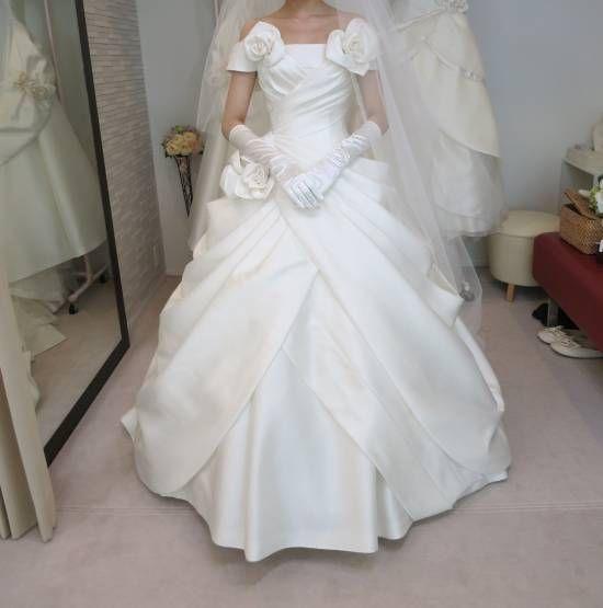 ウェディングドレス〜エマリーエ①〜 オフショルダーとドレープ使いが印象的なドレス。所々に散りばめられた薔薇の花とベルラインが可愛いらしい印象を与えます。