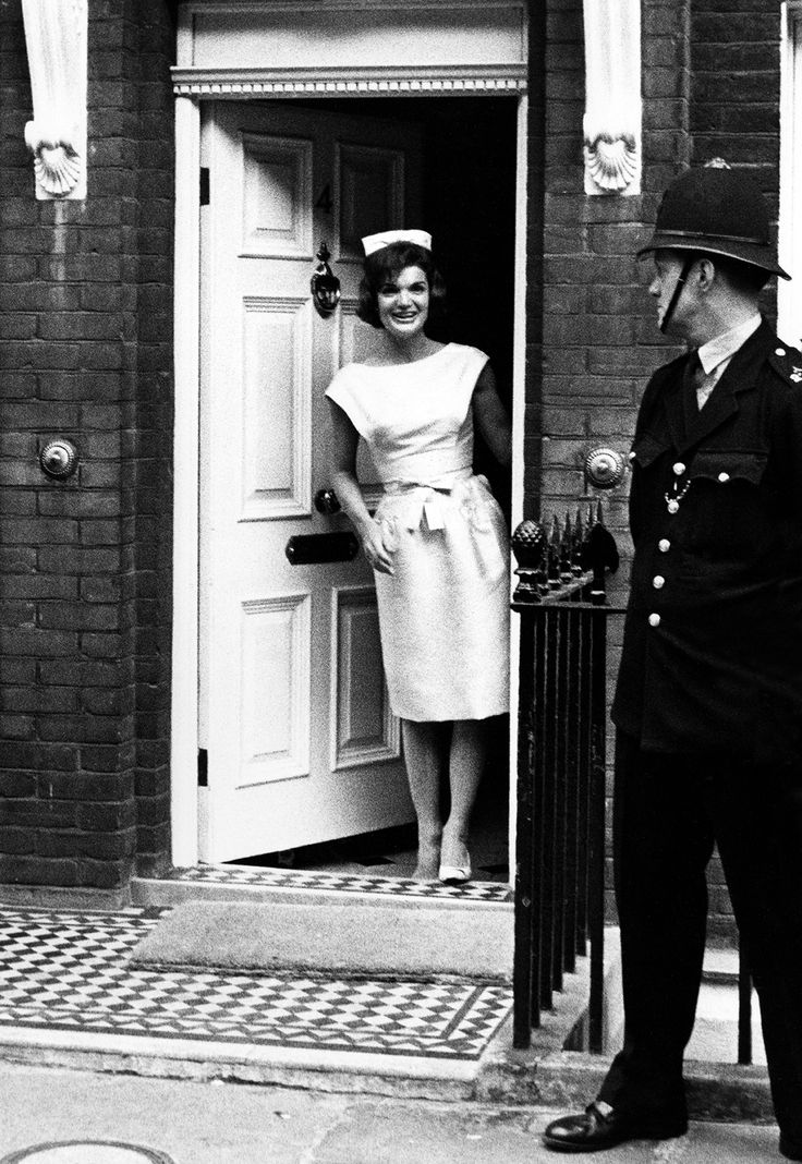 Jackie Kennedy photographed by Harry Benson as she smiles from a doorway in London.