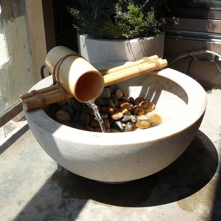 Bamboo fountain made with cut bamboo, twine, and a bamboo cup. Much cheaper than buying premade.