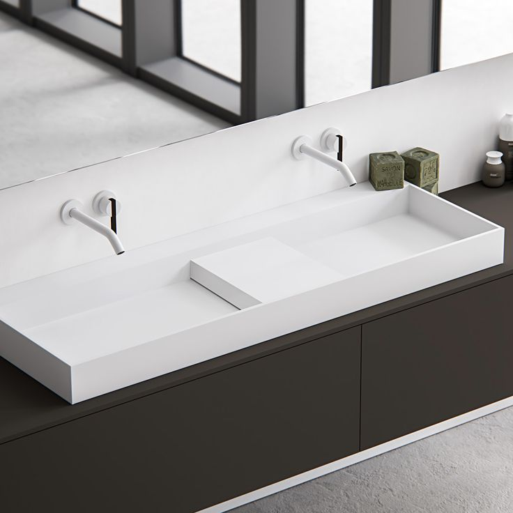 Edge, simple yet sophisticated and characterised by its minimalist rectangular appearance and thin 12mm edge. A completely (hand) made to measure basin out of HI-MACS (solid surface). This basic-shaped basin is ideal for design purposes and easily adaptable. Featured: Edge top mounted basin in Alpine white HI-MACS on top of a Fenix NTM wall mounted cabinet. Divide the basin in two and cover the waste with the divide inlay platform. bathsbyclay.com