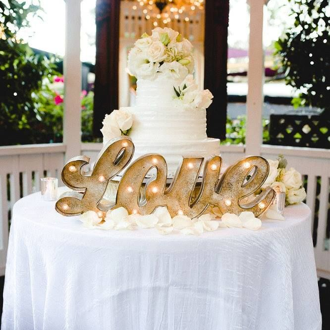 "Let a marquee ""Love"" sign light up a cake table and make it the focal point of the reception ~ http://www.weddingchicks.com/2016/02/09/laguna-beach-tivoli-terrace-wedding/"