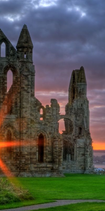 Sunset at: Whitby Abbey is a ruined Benedictine abbey overlooking the North Sea on the East Cliff above Whitby in North Yorkshire, England