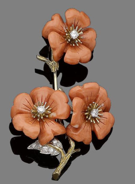 A coral and diamond jabot pin by Boucheron. The bouquet designed as three flowers, each flower head centrally set with a brilliant-cut diamond surrounded by carved coral corallium rubrum petals, signed Boucheron.