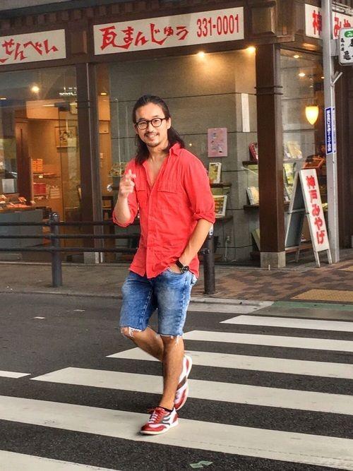 はだけた赤いシャツと赤いスニーカー、自分らしさ全開コーデ。