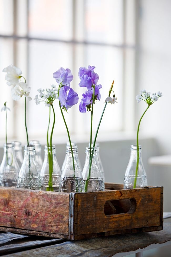 glass coco cola bottles filled with flowers and placed in a vintage wood pop bottle crate