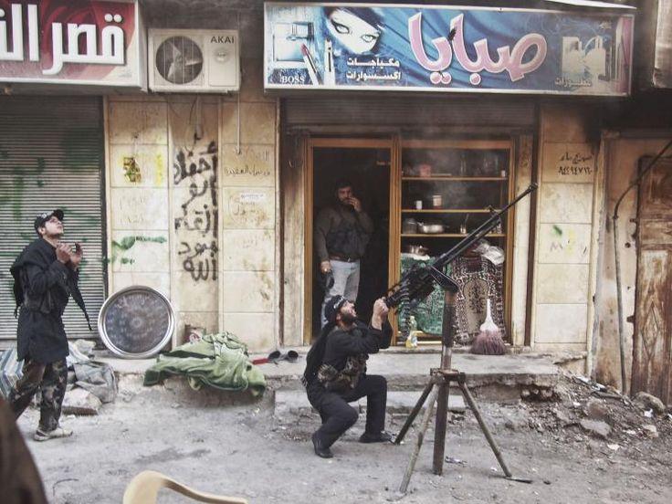 Rebels shoot at a regime warplane during an air raid of rebel positions in the Al-Amiriya district. Aleppo, Syria, March 22, 2013.