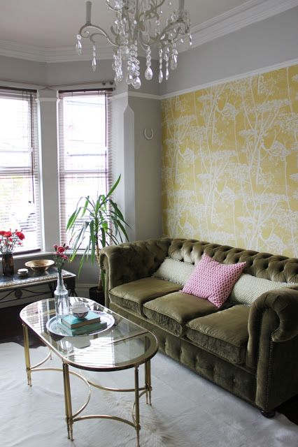 Green 3 seater sofa against the back wall with great wallpaper behind it