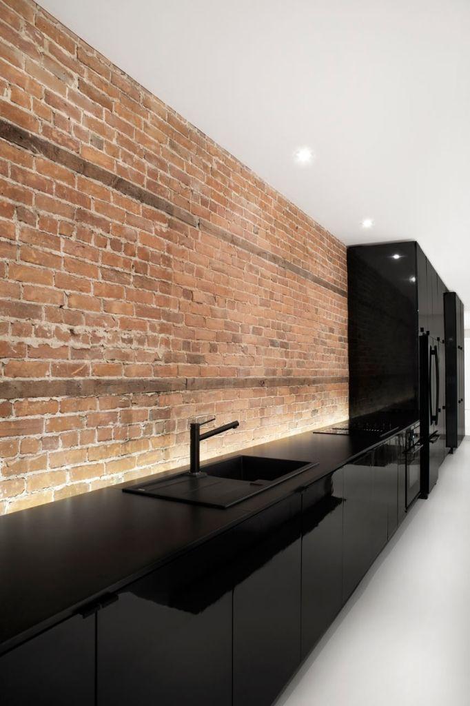 Schwarz lackierte Küche vor roter Ziegelsteinwand