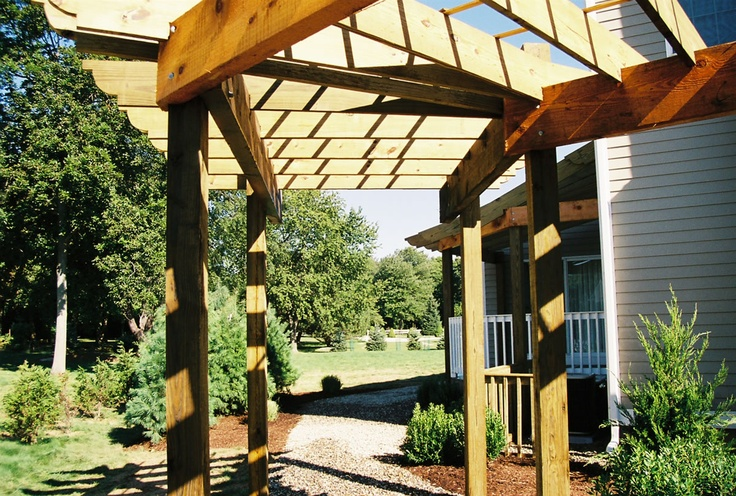 This curving pergola design casts just a bit of shade on the walkway to make ambling through the garden pleasant even in the heat of summer. Design by Land Masters in Fairfield County, CT.