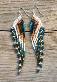 Stunning, nine-strand, shoulder duster earrings measuring about 4 long. Made with Czech Seed Beads featuring blue, turquoise, green, orange,