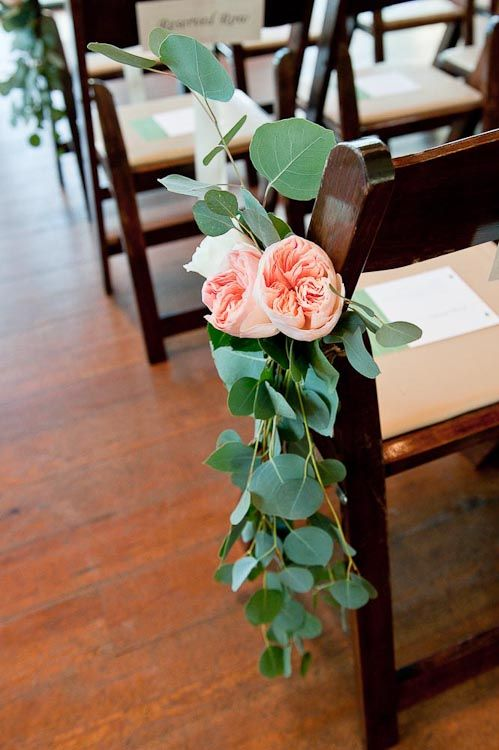 I really like the idea of these flowers with greens cascading down to elongate the decoration on the chair...