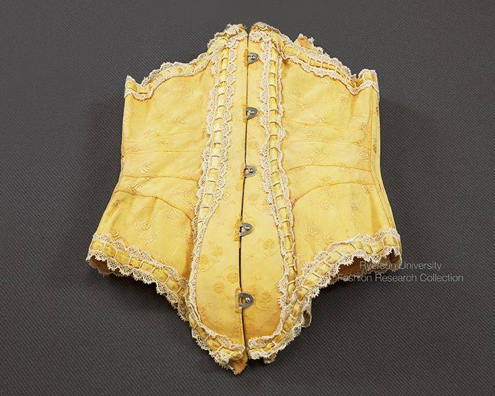 Pumpkin yellow corset with lace and ribbon trim, front busk with metal closures and back eyelets, metal boning channels on side and front. c.1900-1910. FRC2013.05.001