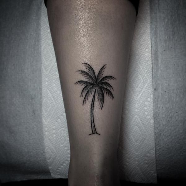 Hand poked palm tree tattoo on the Achilles.
