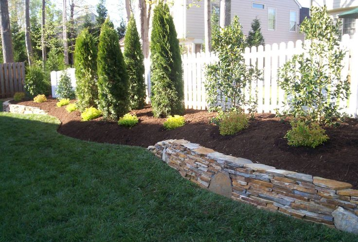 Mojave thin veneer retaining walls with keystones surrounding property border bed with Emerald Green Arborvitae, Nellie Stevens Holly & Little Princess Spirea with aged hardwood mulch