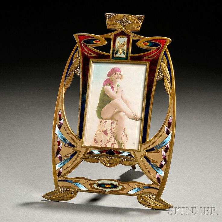 Art Nouveau Enameled Frame  Brass, enamel  Europe, early 20th century  Curvilinear openwork frame accented by vines and berries enamelwork in red, blue, green, and white with back stand.