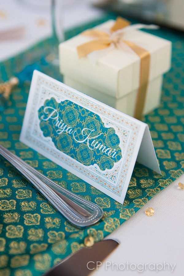 Agra Dreams Asian wedding stationery with matching table favours in teal and gold.  Place cards are starting to become more popular now at Asian weddings so guests now where to be seated.  Ivory with gold ribboned favour boxes with milk chocolate hearts inside make the perfect classic Asian wedding favour for your guests to enjoy and for an extra touch for your tables.  By www.fuschiadesigns.co.uk.