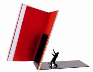 """""""Ah, olamaz! İmdaaat!"""" diyor olmalı ama tabi ki sesi çıkmıyor bu zavallı adamın. Müthiş bir dizayn ile sunulan bu ilginç kitap standına göz attınız mı? Üzerine düşen kitapdan kaçamayan ama çaresizce ona karşı koymaya çalışan bir adam figürü ile tasarlanmış olan bu kitap standını hediye ederek bir erkeği gülümsetebilirsiniz."""