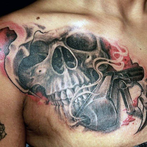 Guy With Evil Skull And Pistol Tattoo On Chest