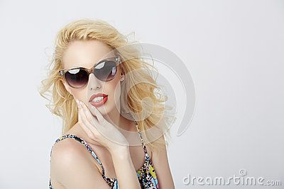Trendy gorgeous blond woman posing with sunglasses on over bright background.