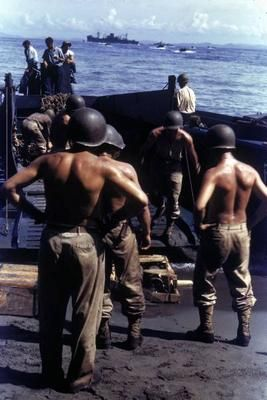Unloading supplies - Helmeted, bare-chested American troops unloading supplies and equipment from landing craft after arrival at Guadalcanal Island,1943