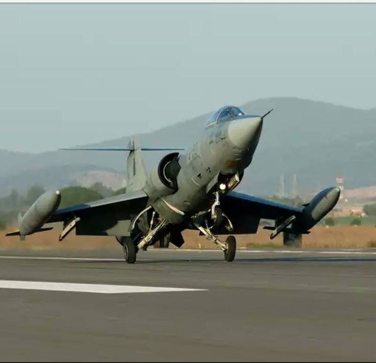 F-104 clearing runway with external wingtip fuel tanks and no weapons under pylons.