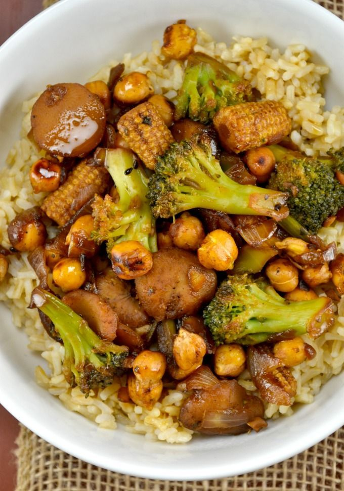 Recipe for a healthy vegan chickpea stirfry bowl with roasted chickpeas, water chestnuts, baby corn, broccoli, fresh garlic and onion and rice.
