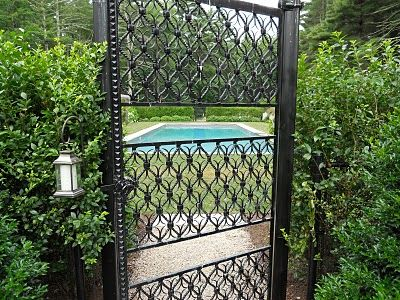 black chain link fence disguised by shrubbery, coupled w/ nice wrought iron gates. Wonder how much something like this would run?