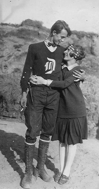 20s era found photo snapshot couple man women teens collegiate casual sports wear vintage fashion college boy girl football player D sweater bow tie jodhpurs skirt shoes scarf hair boots lace up tall knee high pleated