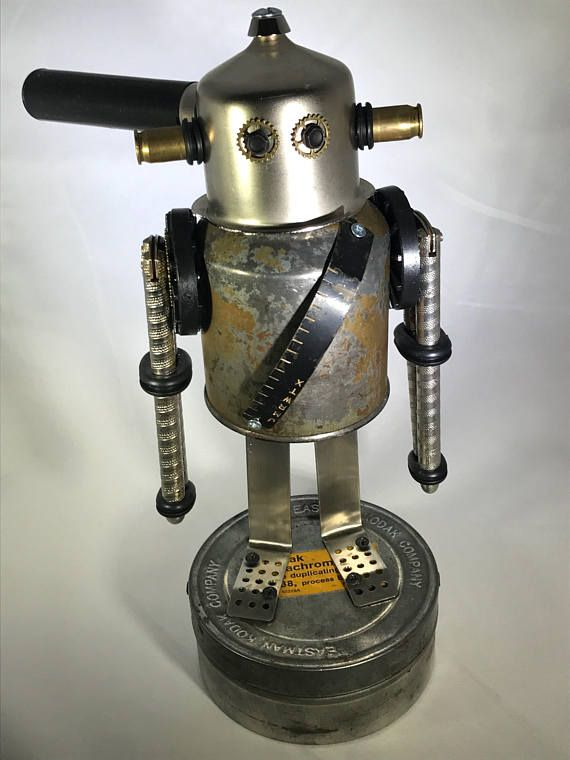 Assemblage bot constructed of found objects. Each of our robots are numbered in the order that they are created. Head is part of an espresso machine with shell casings as antennas. Body is a vintage oil can. Arms are made of nutcrackers. Legs/feet are made of a pair of kitchen tongs - cut in half. Base is a vintage Kodak Eastman film tin. (Note: base is filled with sand and sealed to counterbalance the weight of the robot.) Assembled using stainless hardware. Overall Dimensions are: 1...