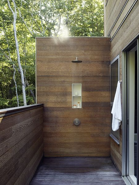 A wood-linedoutdoor shower adds a modern touch to one of the decks.  Photo by: Richard Powers
