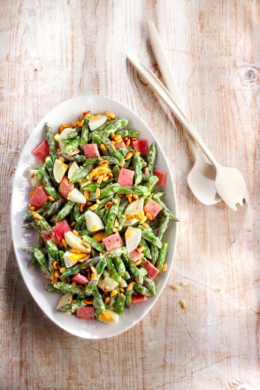 Schep asperge, ham en ei door elkaar. Klop de ingrediënten voor de dressing door elkaar en breng op smaak met zout en versgemalen peper. Schep dit door de salade en doe over in een schaal. Bestrooi de salade met pijnboompitten en nog wat versgemalen peper.