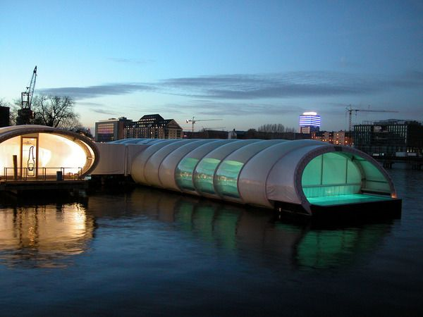 """The Badeschiff. Berlin, Germany. Badeschiff or """"bathing ship"""" is the most unusual swimming pool in Berlin. It is an old cargo container converted into a pool on Spree River. During the summer it is an outdoor pool with the beach, bar and DJs. In the winter the whole thing is covered, and a few extra saunas are added."""