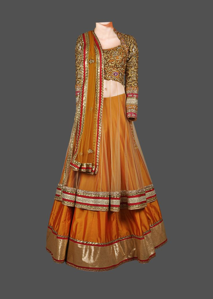 This golden color lehenga choli is featuring in net fabric with a long, full sleeve, hand embroidered net blouse, and a silk skirt. It is paired with a four sid