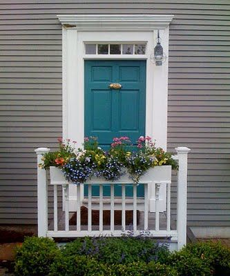 Medium gray house with dark turquoise door.  I kind of love this. white trip. dark gray or black shutters